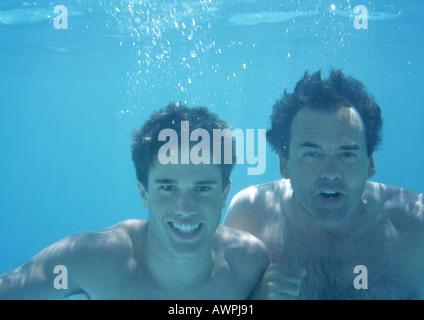 Mann und Teenager unter Wasser. - Stockfoto