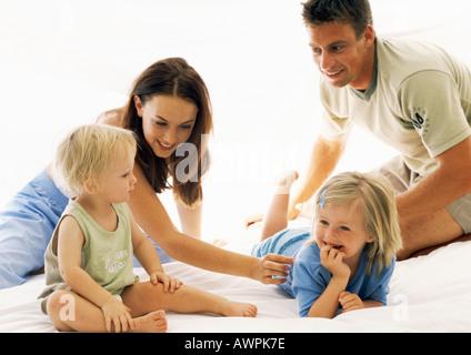 Familie zusammen im Bett, Eltern kitzeln kleines Mädchen - Stockfoto
