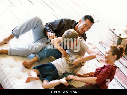 Eltern und Kinder spielen auf Matratze - Stockfoto