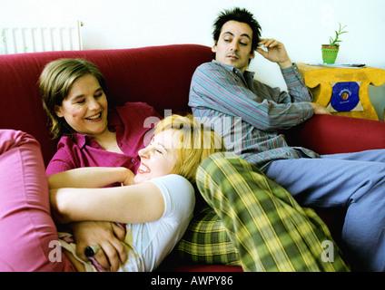 Zwei Frauen spielen auf Sofa, Mann sitzend zu beobachten. - Stockfoto