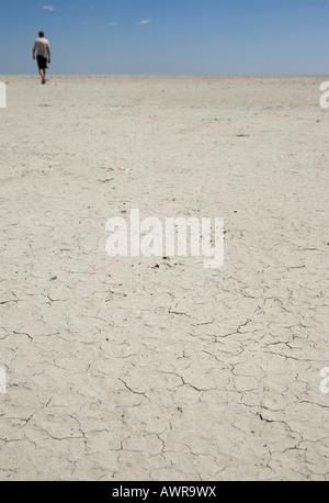 Ein Mann geht über die gebackenen Schlamm der ephemere Sua Pan, eine Salzpfanne in der Nähe von Nata in der Kalahari - Stockfoto