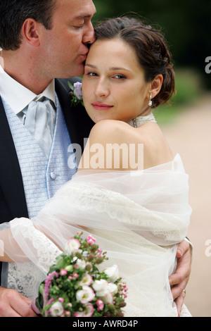 Schöne lächelnde Braut im weißen Kleid mit Schleier am Tag der Hochzeit ihr neuen Mann kuscheln - Stockfoto