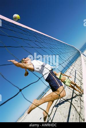 Zwei junge Frauen spielen Beach-Volleyball, eine in der Luft. - Stockfoto