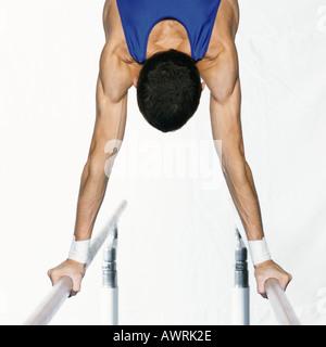 Männliche Turnerin Durchführung Handstand am Barren, Rückansicht, beschnitten - Stockfoto