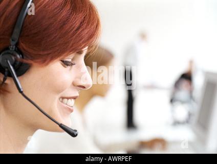 Frau trägt Kopfhörer im Büro, Seitenansicht, Nahaufnahme - Stockfoto