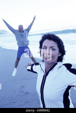 Reifer Mann und Frau am Strand dehnen - Stockfoto