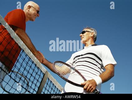 Zwei reife Männer Händeschütteln über Tennis net, niedrigen Winkel Ansicht - Stockfoto