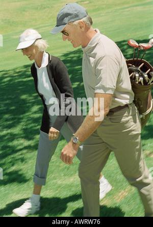 Reifer Mann und Frau auf grün, Mann mit Golfschläger - Stockfoto