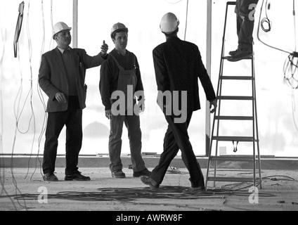 Drei Männer tragen Schutzhelme auf der Baustelle - Stockfoto