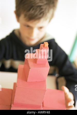 Kind hinter Stapel von Blöcken, Fokus auf Vordergrund - Stockfoto