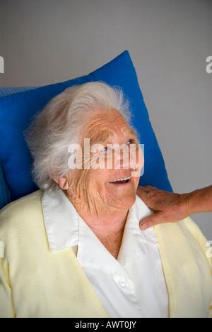 Glücklich lächelnd senior Alter ältere Dame mit tröstenden Hand der Pflegeperson Begleiter auf ihrer Schulter - Stockfoto