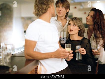 Junge Männer und Frauen trinken in Bar - Stockfoto