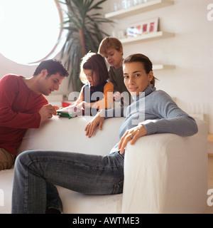 Mutter sitzt vor Familie, spielen im Hintergrund - Stockfoto