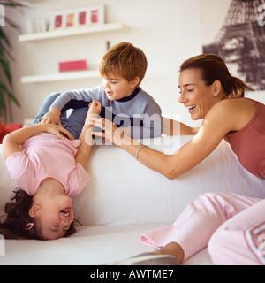 Kinder spielen mit Mutter auf couch - Stockfoto