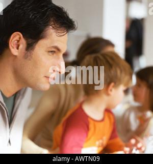 Vater sitzt mit Familie, Nahaufnahme - Stockfoto