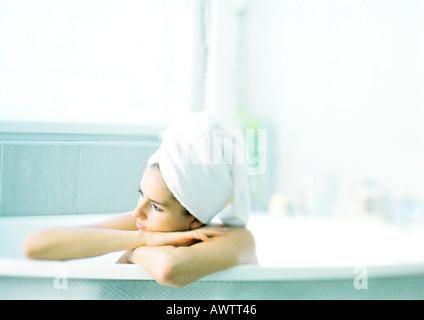 Frau in der Badewanne stützte sich auf den Wannenrand, Haare im Handtuch eingewickelt - Stockfoto