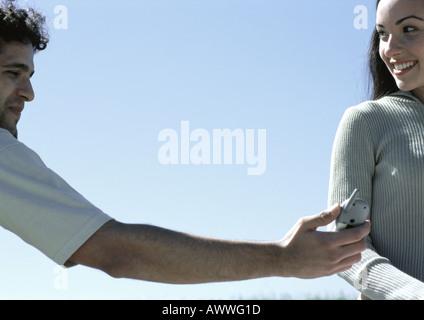 Junger Mann Übergabe Handy auf eine junge Frau mit Himmel im Hintergrund - Stockfoto