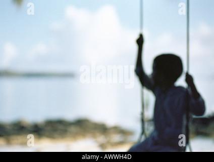 Silhouette des Kind sitzt auf Schaukel, unscharf - Stockfoto