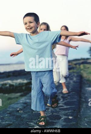 Kinder Wandern einzelne Datei mit Armen - Stockfoto