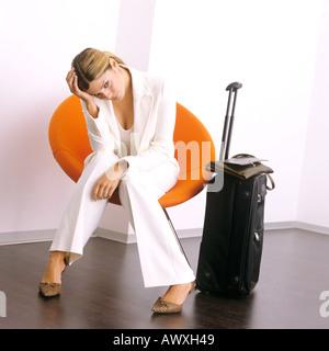 junge Geschäftsfrau warten im Liegestuhl mit Gepäck suchen gelangweilt und frustriert - Stockfoto