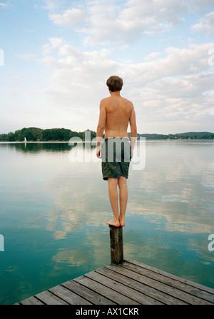 Ein Mann steht auf einem Steg am See - Stockfoto