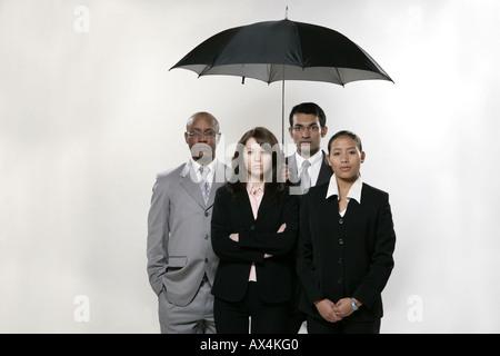 Porträt von vier Geschäftsleuten stehen unter einem Regenschirm - Stockfoto