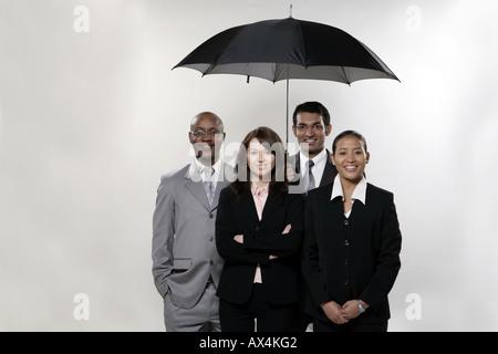 Porträt von vier Geschäftsleuten stehen unter einem Regenschirm und lächelnd - Stockfoto