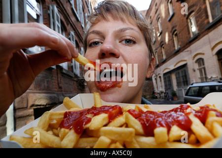 Junge Frau isst Pommes Frites mit ketchup - Stockfoto