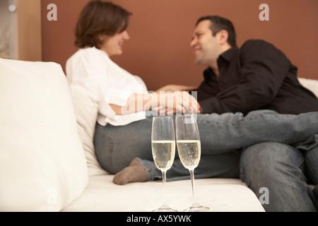 Junges Paar liebevoll blickt in die Augen, zwei Sektgläser im Vordergrund - Stockfoto