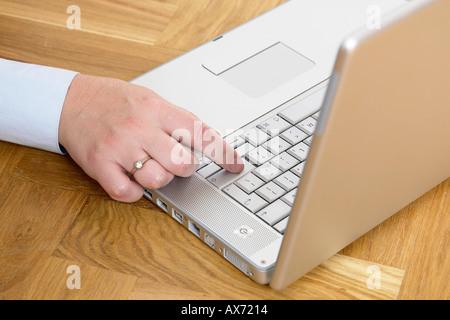 Nahaufnahme eines Unternehmens Womans Hand Arbeiten von zu Hause mit Laptop im hölzernen Dachboden Stock - Stockfoto