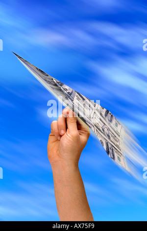 Hand, die bunte Papierflieger aus Geld gemacht - Stockfoto