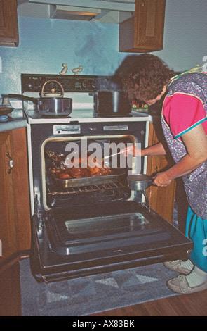Hausfrau, eine goldene braune Türkei, Heften, wie sie kocht Abendessen am Thanksgiving Day für ihre Familie, die - Stockfoto