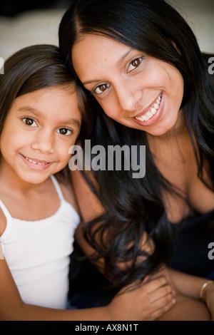 Mutter und Tochter halten einander durch Fensterlicht. - Stockfoto