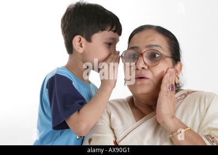 Jungen Flüstern in den Ohren von seiner Großmutter - Stockfoto