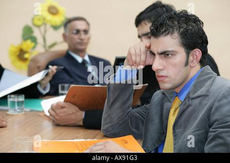 Seitenansicht eines Geschäftsmannes sitzen und denken in einer Besprechung - Stockfoto