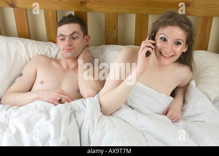ein Mann ist mit seiner Frau im Chat auf ihrem Handy im Bett satt - Stockfoto