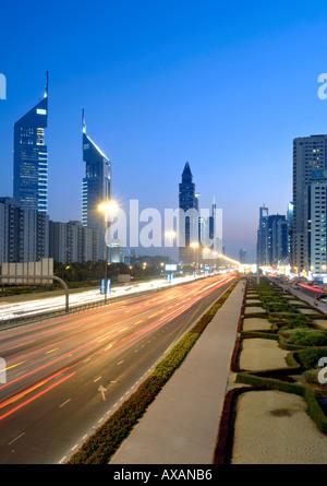 Ein Sonnenuntergang Blick auf Verkehr Wanderwege und die Gebäude entlang der Sheikh Khalifa Bin Zayed Road in Dubai. - Stockfoto