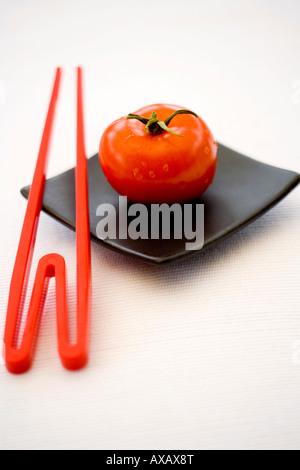 Eine rote Tomaten und roten Stäbchen auf einem quadratischen schwarzen orientalische Teller - Stockfoto