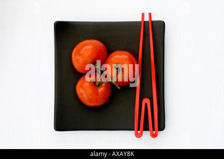 Drei rote Tomaten auf einem schwarzen Quadrat orientalische Teller mit roten Stäbchen - Stockfoto