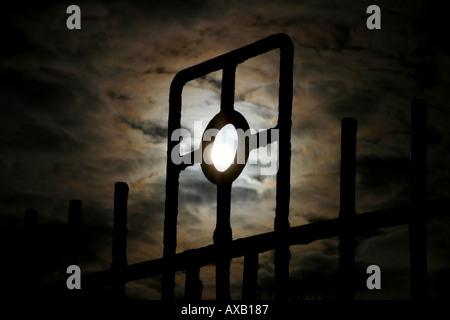 Die Sonne scheint durch einen Friedhof Zaun - Stockfoto