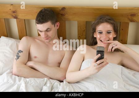 ein Mann ist mit seiner Frau, SMS-Nachrichten auf ihr Handy im Bett lesen satt - Stockfoto