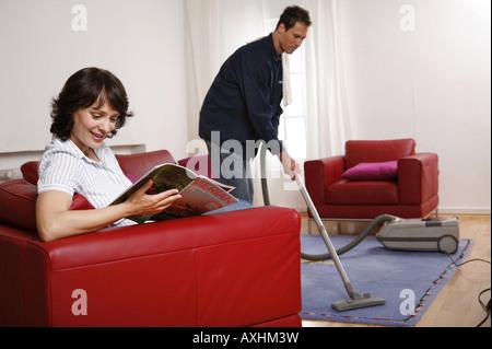 Symbole der Partnerschaft er saugt den Teppich, während sie eine Zeitschrift liest - Stockfoto