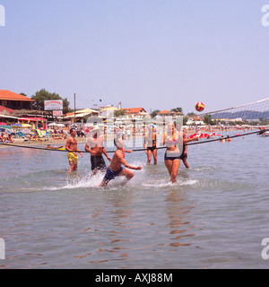 Gruppe von Jugendlichen spielen Beach-Volleyball im seichten Wasser am Rand von Laganas Beach Südküste Zakynthos - Stockfoto