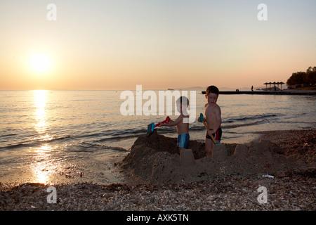 Zwei jungen Kindern Brüder spielen, bauen eine Sandburg am Strand am Meer in Saronida Attika oder Atiki Griechenland - Stockfoto