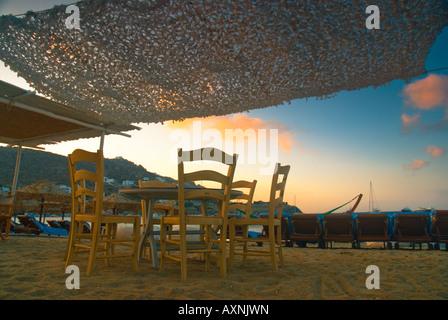 Ein Tisch mit Stühlen mit Blick auf das Meer in Ornos, Insel Mykonos, Griechenland einrichten - Stockfoto