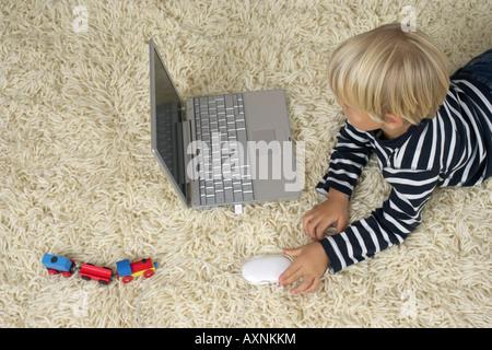 Junge (4-5 Jahre) am Boden liegend und mit einem laptop - Stockfoto