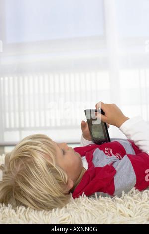 Junge (4-5 Jahre) am Boden mit einem handheld liegen - Stockfoto