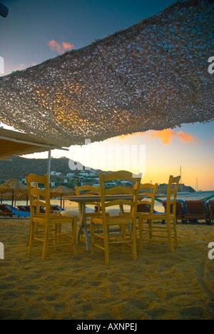 Ornos Beach, Insel Mykonos, Griechenland. Entspannen am Strand von Ornos in Griechenland bei Sonnenuntergang. - Stockfoto