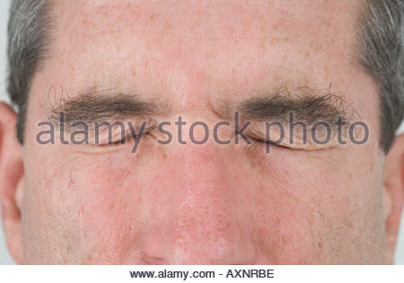 Nahaufnahme von einem mittleren Alters mans Gesicht mit seinen Augen fest geschlossen - Stockfoto