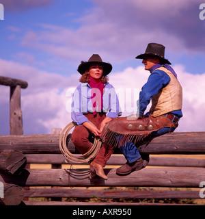 Cowgirl und Cowboy sitzt auf einem Holzzaun Log Corral - Stockfoto